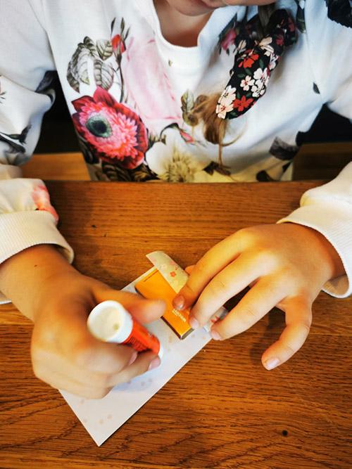 Lia beklebt die Zündholzschachtel mit einem schönen Papier